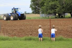 Children watching a tractor